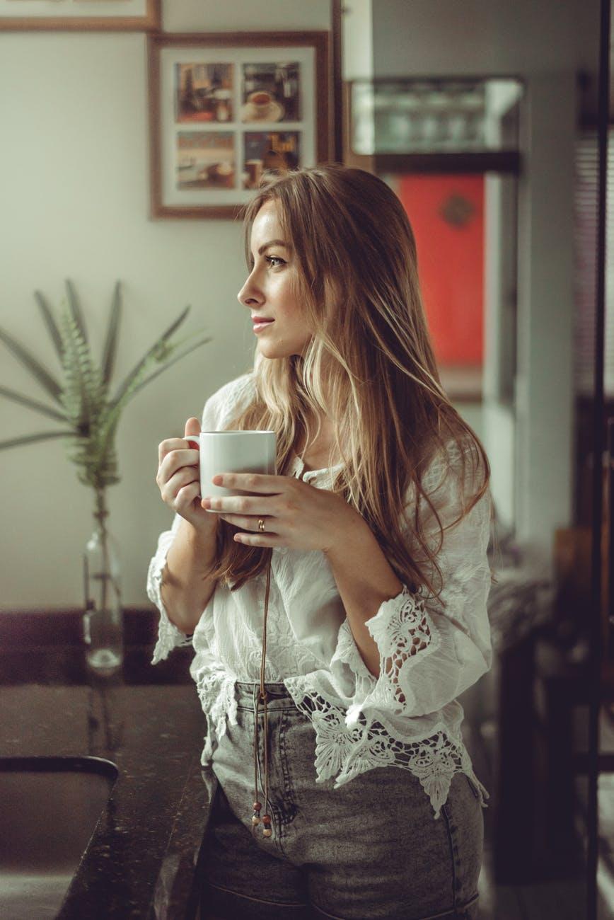 photo of woman holding mug
